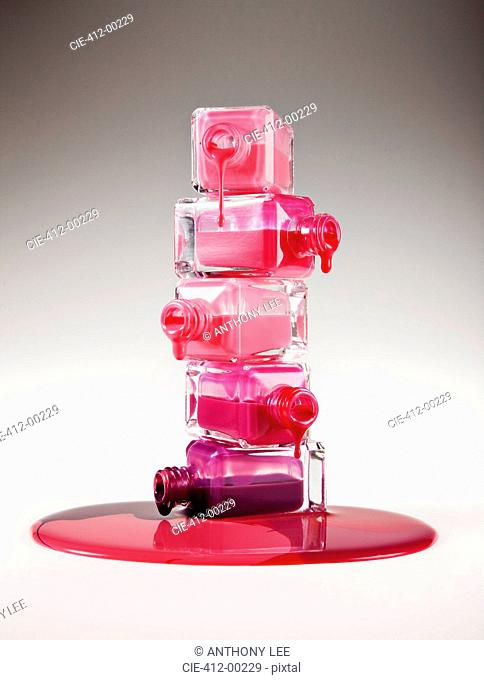 Multicolor fingernail polish dripping from stacked bottles