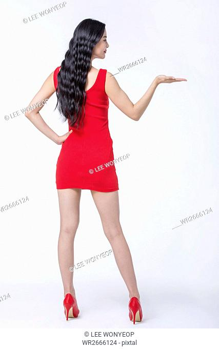 Back of young woman with long wavy hair in red dress and in red shoes posing