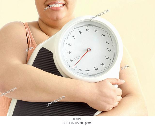 Overweight woman holding weighing scales