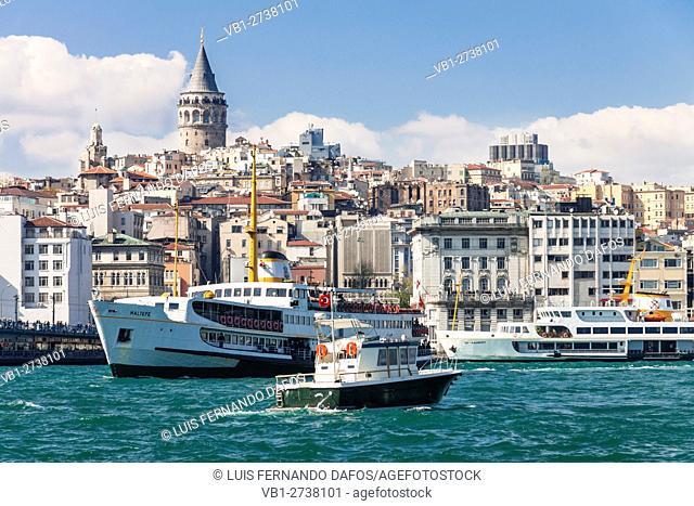 Turkey, Istanbul. Passenger ferries and boats sailing on the Golden Horn with Galata Tower in background