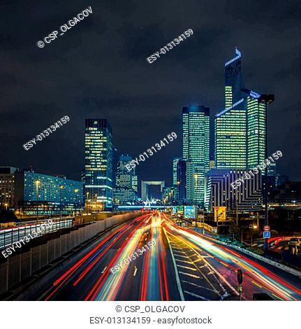 Night road with skyscrapers of La Defense, Paris, France