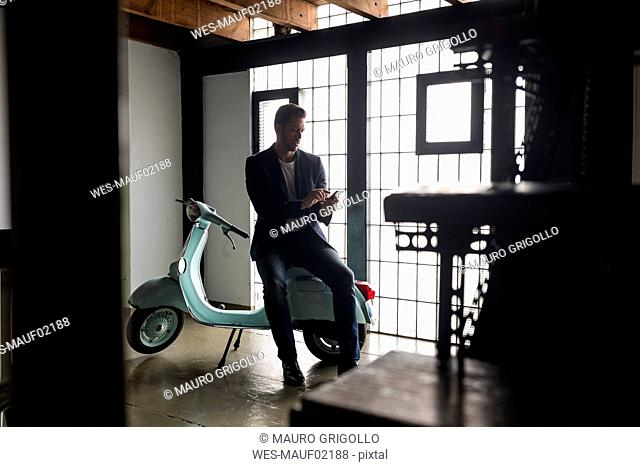 Man with motor scooter in a loft using cell phone