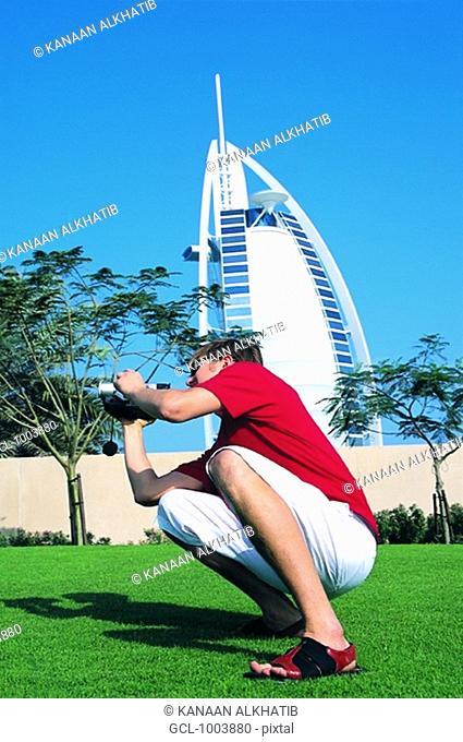 Western tourist taking pictures in front of Burj Al Arab hotel in Dubai, UAE