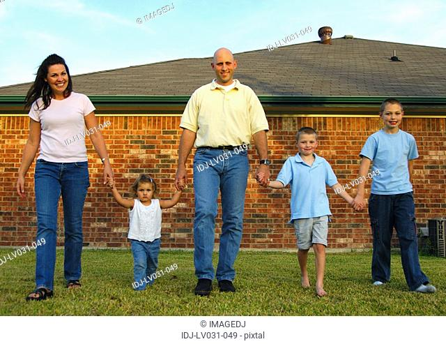 Mid adult couple walking in a park with their three children