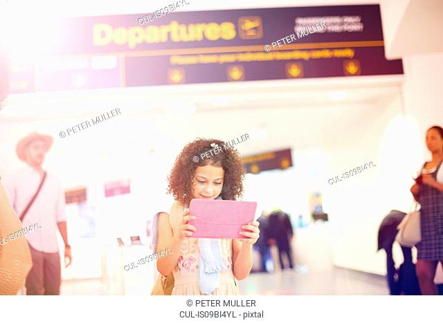 Young girl at departure lounge in airport, using digital tablet