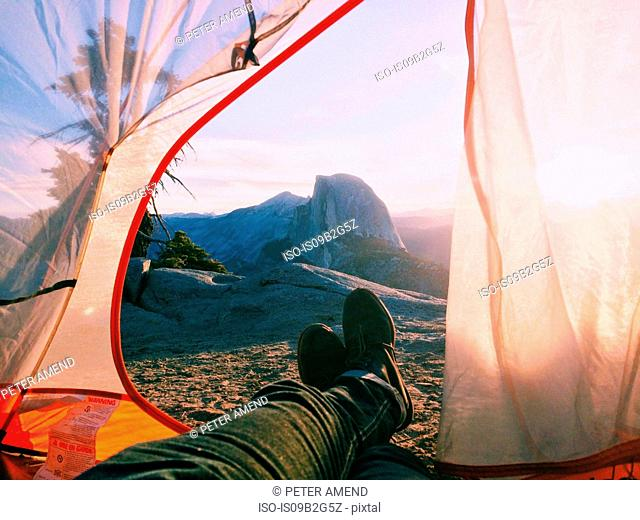 Pair of legs sticking out of tent, mountains in background, Yosemite National Park, California, USA