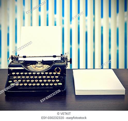 Vintage typewriter with stack of blank paper on table