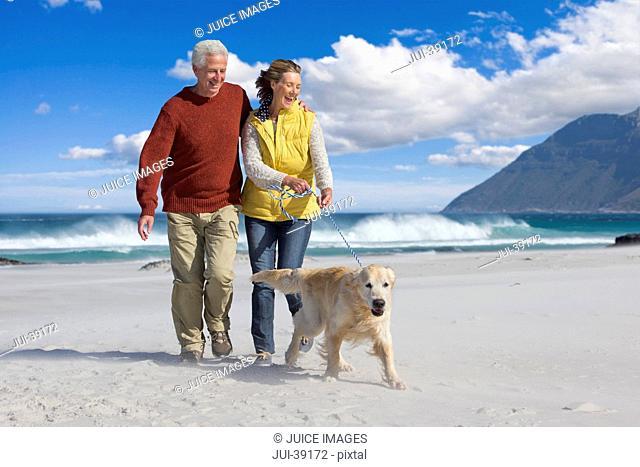 Happy senior couple with dog on sunny beach