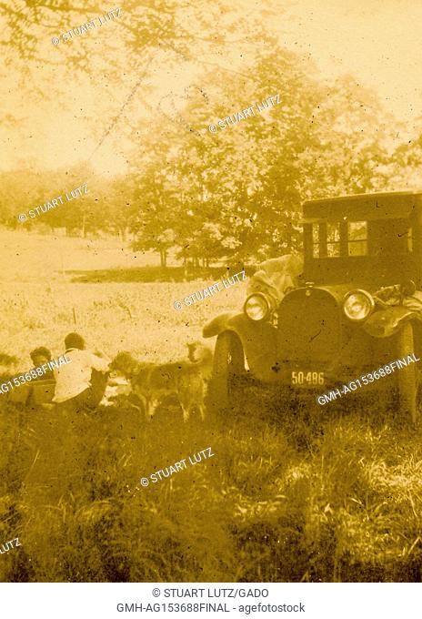 A family with their dog picnics in a field beside their automobile during a road trip through New England, 1927. ()