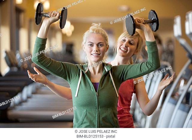 Caucasian woman working with trainer in gym