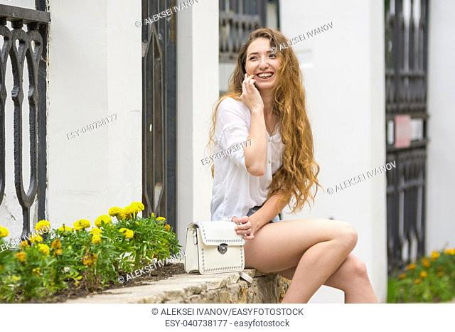 Young girl having fun on the phone in the street