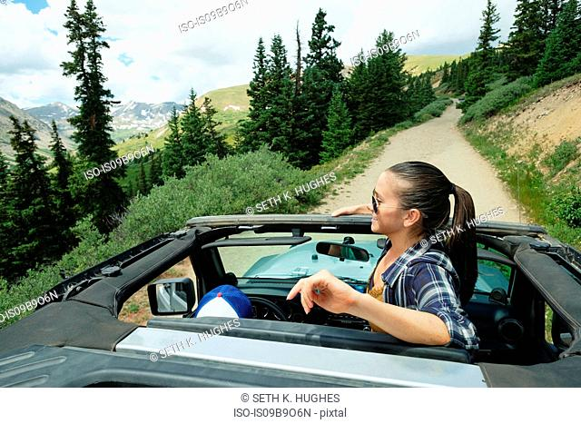 Young woman looking out from four wheel convertible in Rocky mountains, Breckenridge, Colorado, USA