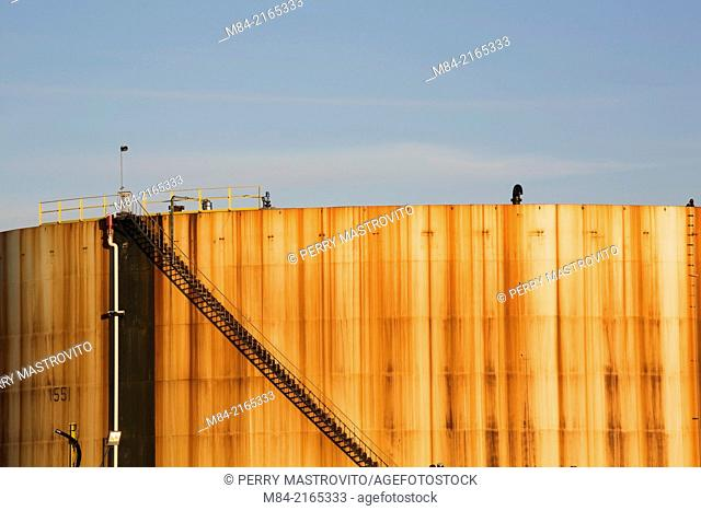 Rusted oil storage tank with black metal staircase at an oil and gas refinery, Montreal, Quebec, Canada