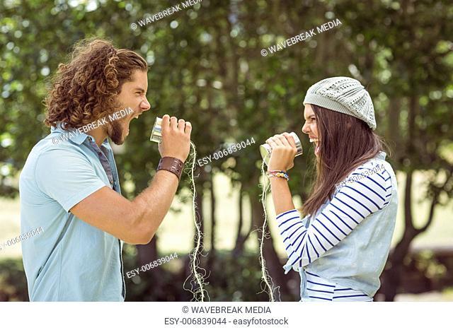 Young couple shouting through tin cans