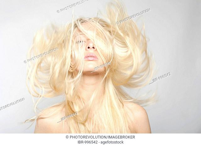 Young woman with blond hair flying on grey