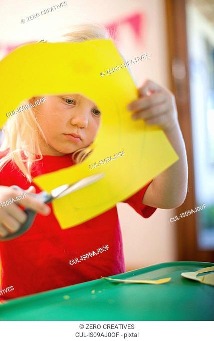 Girl cutting out cardboard shapes at nursery school