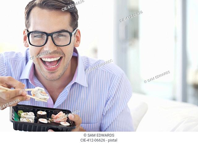 Businessman eating sushi in office