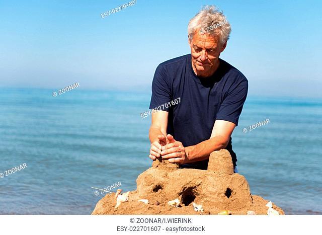 Elderly man with sand castle