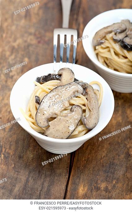 Italian spaghetti pasta and fresh wild mushrooms on rustic wood table