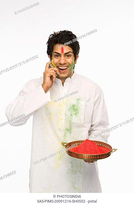 Man holding Holi colors and talking on a mobile phone