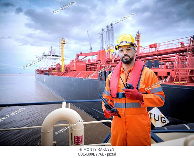 Composite image of ship worker on tugboat with oil tanker