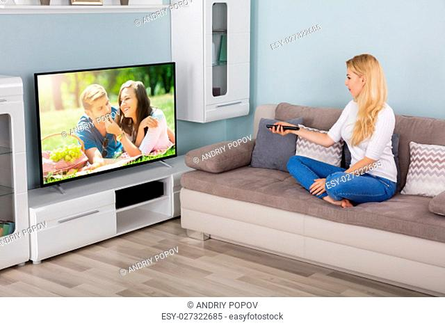 Young Woman Watching Movie On Television At Home