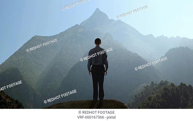 Long shot of businessman raising his arms in praise while looking at a mountain, Marbella region, Spain