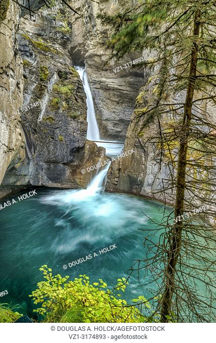 Turquoise water flows over Johnston Canyon Trail Lower Falls Banff National Park Canada