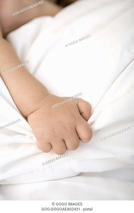 Baby clutching sheets