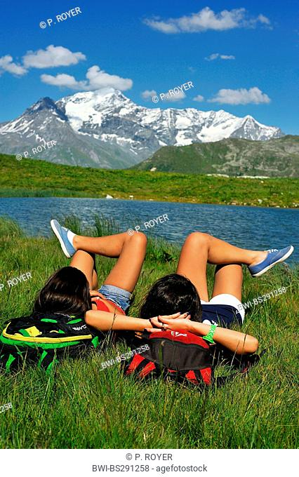 two young woman lying on mountain meadow at lake Carolay and enjoying a good view, France, Vanoise National Park