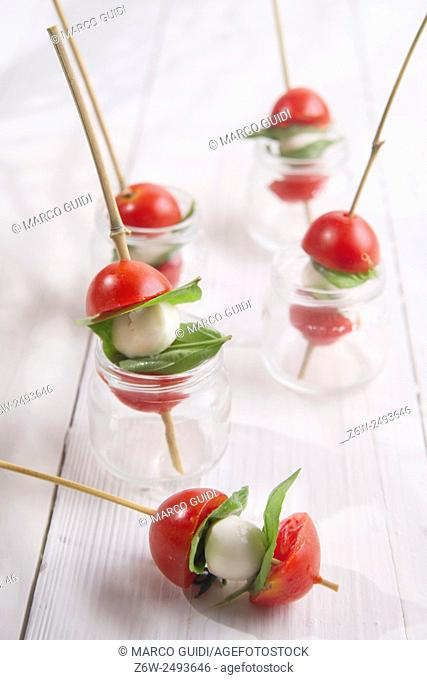 Presentation of small skewer caprese, tomato mozzarella and basil