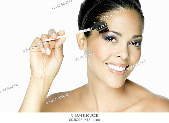 Woman using eyebrow comb