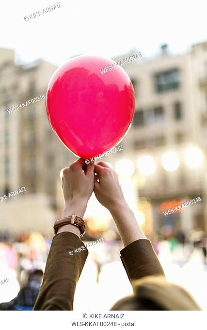 Woman's hands holding pink balloon