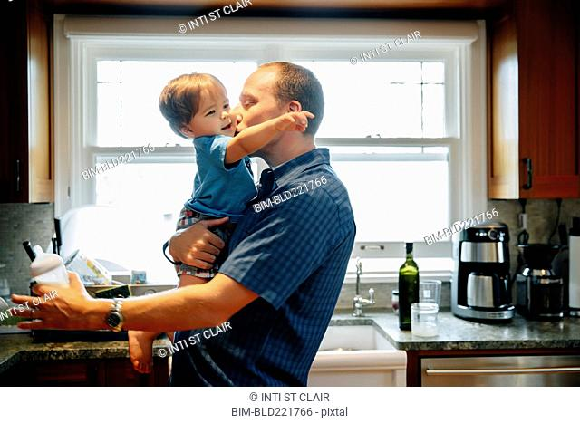 Father kissing baby son in kitchen