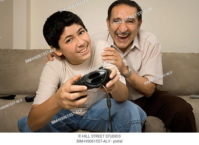 Hispanic grandfather laughing while grandson plays video game
