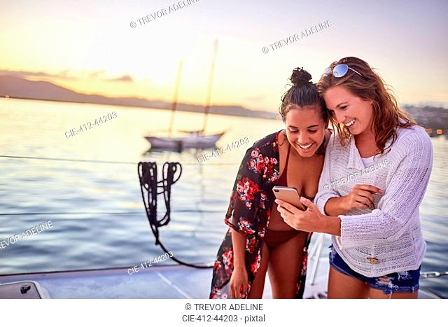 Young women friends using smart phone on boat
