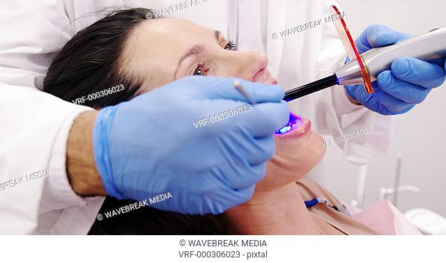Dentist examining female patient with dental curing light