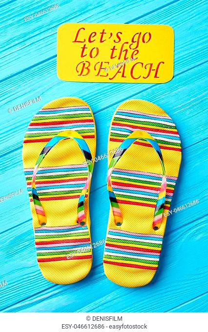 Text and slippers, blue surface. Pair of female flip-flops. Summer beach footwear