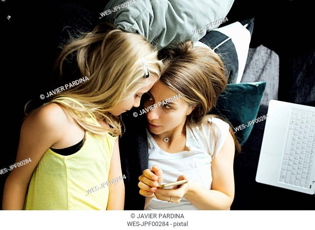 Relaxed mother and daughter with cell phone on sofa