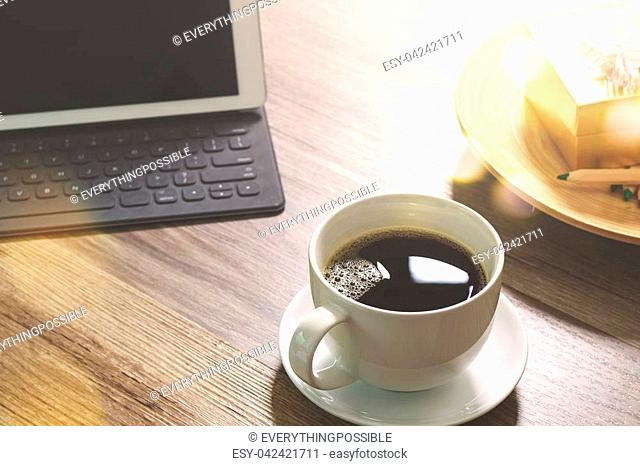 Coffee cup and Digital table dock smart keyboard,gold gift box and round wood tray,color pencil on wooden table,filter effect