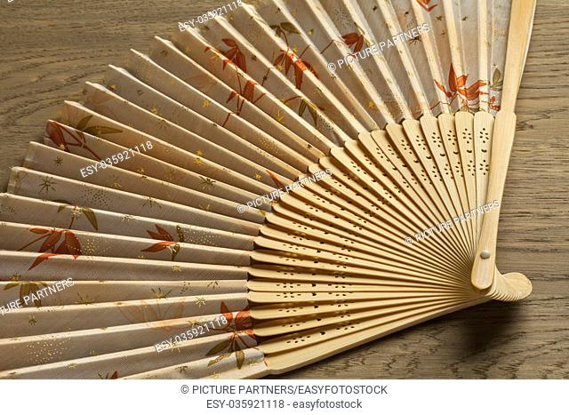 Traditional Japanese hand fan decorated with autumn maple leaves