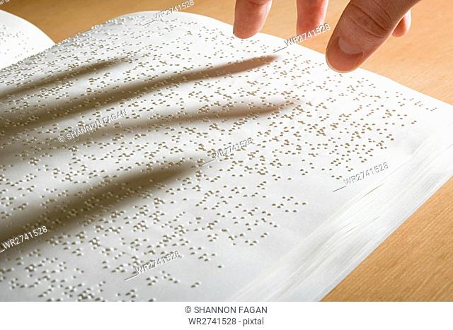 Fingers above a braille book