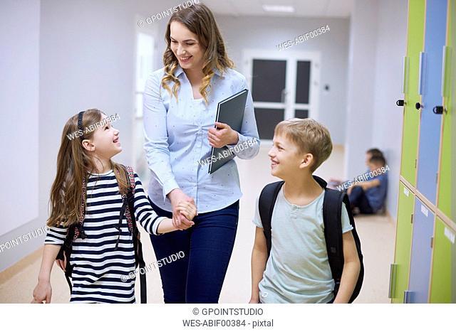 Smiling pupils and teacher walking hand in hand on corridor in school