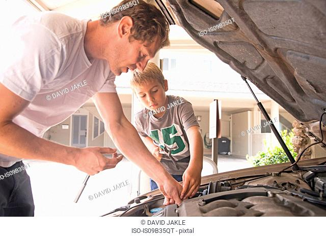 Father showing son car maintenance under car hood