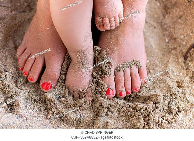 Mother with baby daughter's bare feet in sand
