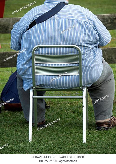 obese man sat on a small chair at an outdoor event, Britain