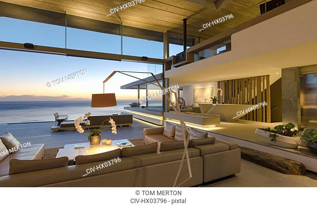 Illuminated modern, luxury home showcase interior living room with ocean view at dusk