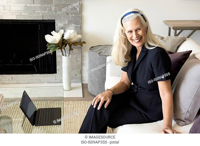 Portrait of senior female businesswoman sitting on sofa, smiling