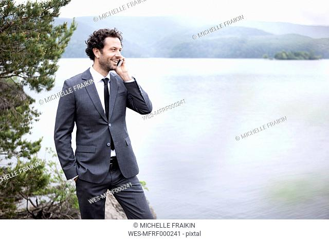 Germany, Rur Reservoir, smiling businessman at lakeshore on cell phone