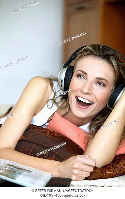 Wohnzimmer Frau Lachen Mimik Musik Hoeren Kopfhoerer Innen Zuhause Boden Liegen Freizeit Erholung Erholen Entspannung Entspannen Lifestyle Portrait